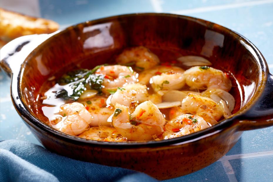 """Eins meiner liebsten Tapas-Rezepte sind die """"Gambas Pil Pil"""", das sind Garnelen in Knoblauchöl, kochend heiß in der typischen bräunlichen Tonschale serviert."""
